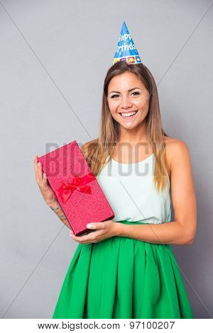 Happy cute girl in party hat holding gift box over gray background and looking at camera