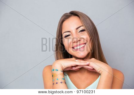 Portrait of a smiling attractive girl on gray background. Looking at camera