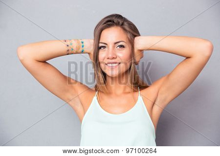 Smiling young woman covering her ears over gray background and looking at camera