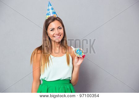 Happy young girl in birthday hat and whistle standing over gray background and looking at camera