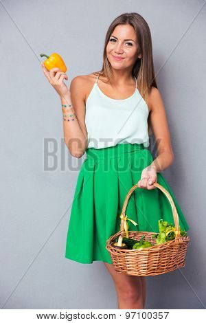 Portrait of a happy cute woman holding basket with vegetables over gray background