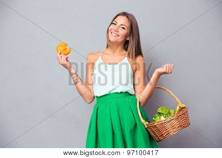 Portrait of a happy charming woman holding basket with vegetables and bagel over gray background