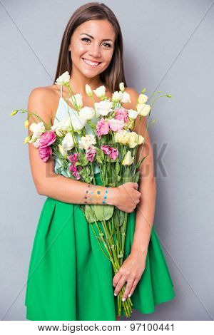 Smiling beautiful woman holding flowers over gray background. Looking at camera
