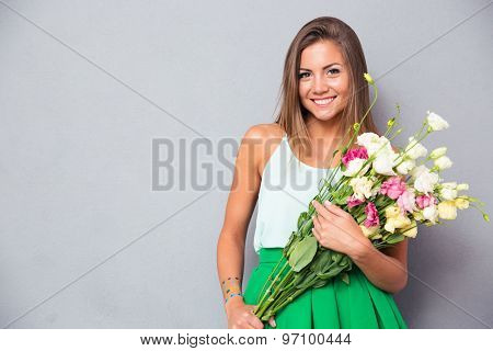 Portrait of a cute happy woman holding flowers over gray background. Looking at camera