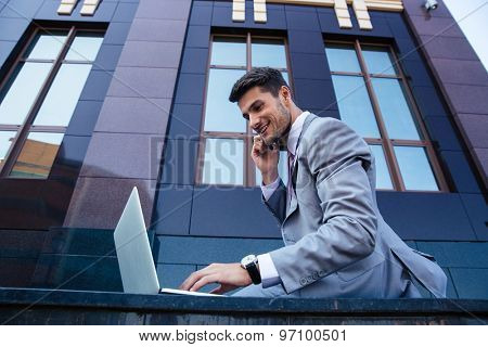 Happy businessman talking on the phone and using laptop outdoors