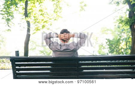 Back view portrait of a businessman resting on the bench outdoors