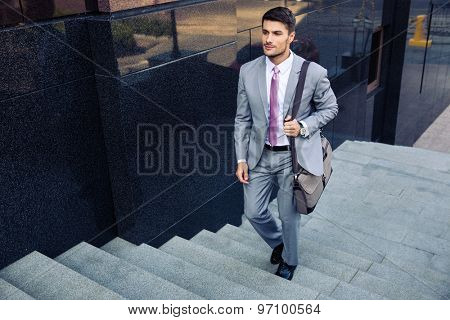 Confident businessman walking on stairs outdoors