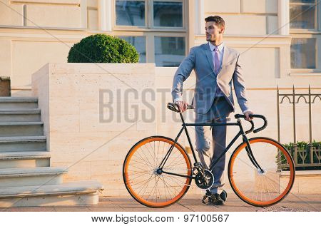 Portrait of a handsome businessman standing outdoors with bicycle and looking away