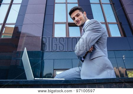Portrait of a happy businessman with laptop outdoors. Looking at camera