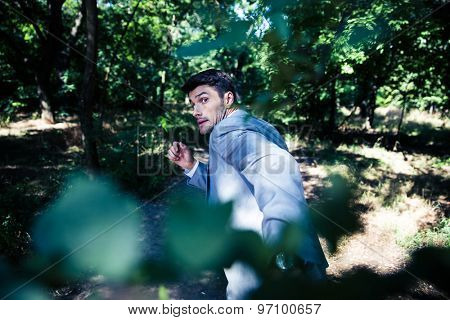Afraid businessman running away from something outdoors in park