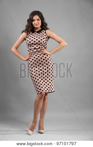 Portrait of young pretty woman in beige dots dress on grey background