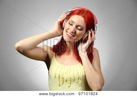 Beautiful young woman with headphones on gray background