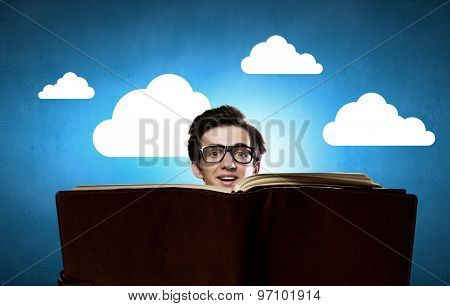 Young man in glasses with opened book in hands