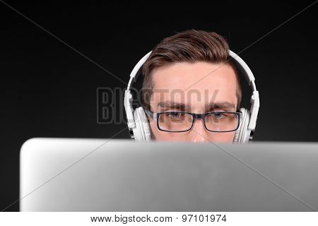 Handsome young man with laptop on grey background