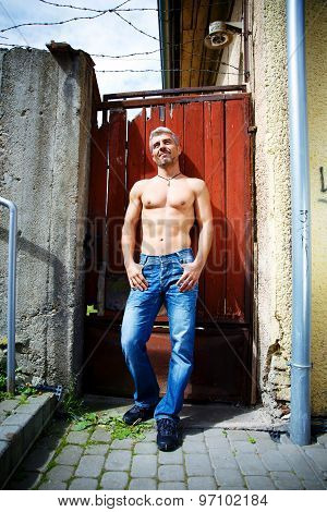 Sexy Fashion Portrait Hot Male Model In Stylish Jeans With Muscular Body Posing. Wolves Tooth Jewele