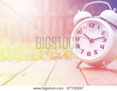 Classic Alarm Clock On Wood Against Nature Background