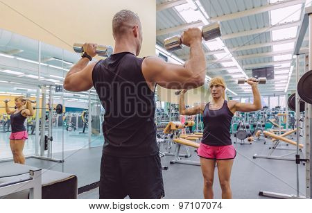 Man coach training to woman with dumbbells exercises