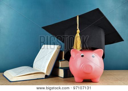 Piggy bank with book and grad hat on blackboard background