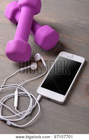 Mobile phone and earphones with dumbbells on wooden table, closeup