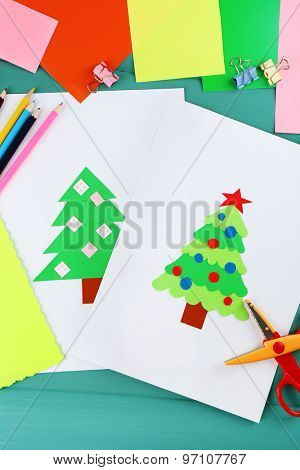 Creative paper Christmas tree on white paper sheet, scissors and colorful crayons on color table background