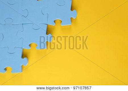 Puzzle pieces on yellow background