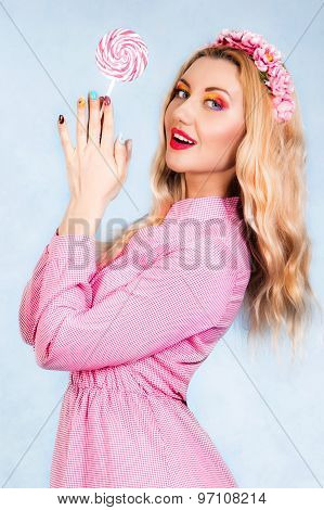 Cute Young Woman In A Pink Dress Holding A Candy