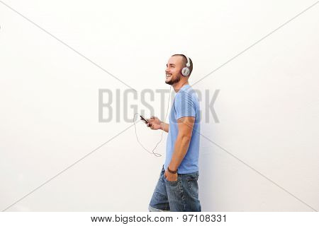 Man Walking With Mobile Phone Listening To Music On Headphones