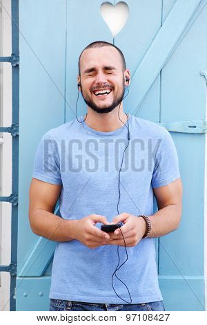 Man Listening With Earphones On Mobile Phone And Laughing