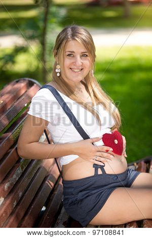 Portrait Of Happy Pregnant Woman Posing With Knitted Heart