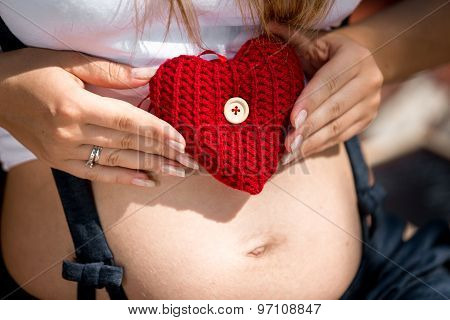 Closeup Of Young Pregnant Woman Holding Red Heart On Abdomen