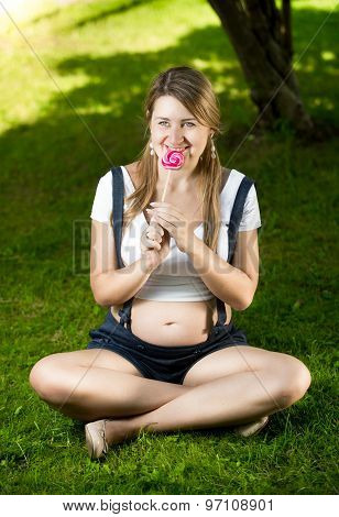 Pregnant Woman Sitting On Grass At Park And Licking Candy