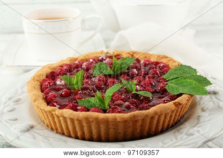Tart with raspberries and tasty tea, on color  wooden background