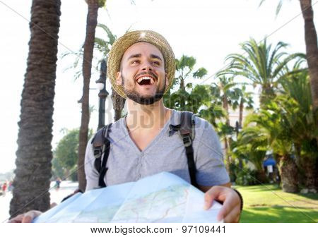 Young Man With Backpack On Vacation Laughing With Map