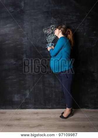 Pregnant Woman Smelling Flowers Drawn By Chalk On Big Black Wall