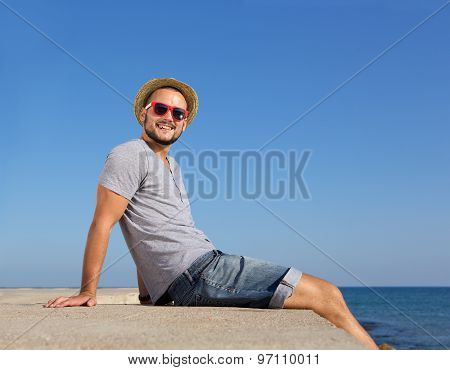 Happy Young Man Sitting By The Sea In Summer With Hat