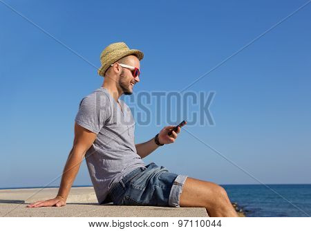 Happy Young Man Sitting By The Sea With Mobile Phone