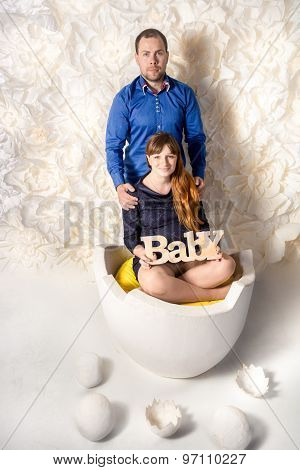 Expecting Parents Posing At Big Egg Shell With Decorative Eggs