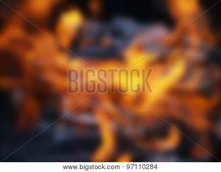 Blurred burning charcoal embers firewood with ashes and flames