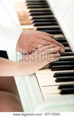 Toned Photo Of Bride And Groom Wearing Rings Playing On Piano