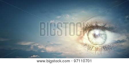 Close up of female eye on blue sky background