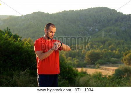 Healthy Sports Man Standing Outdoors Looking At Watch