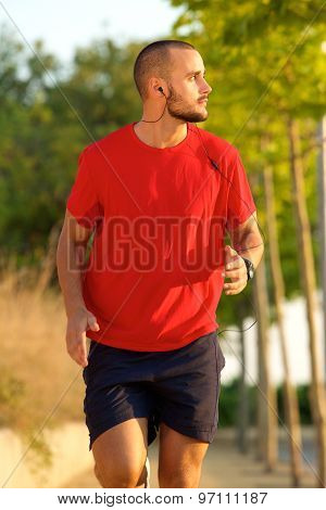 Young Man Running With Earphones Outside