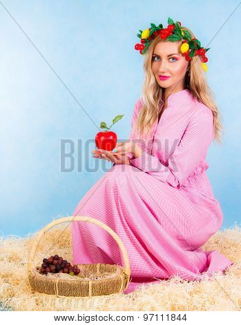 Beautiful Young Woman In A Pink Dress Sitting In A Hay