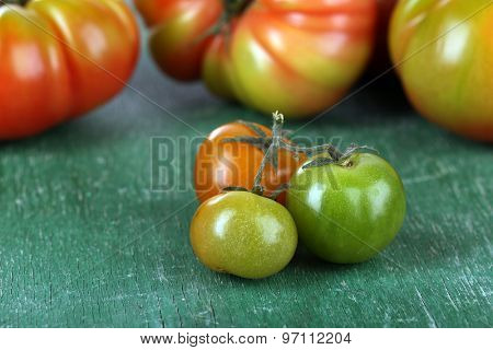 Green tomatoes on wooden table close up