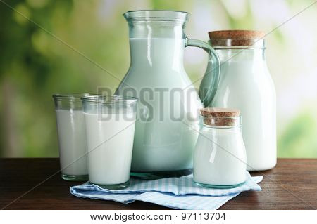 Pitcher, jars and glasses of milk on wooden table, on nature background