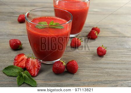 Glasses of strawberry smoothie with berries on wooden table close up