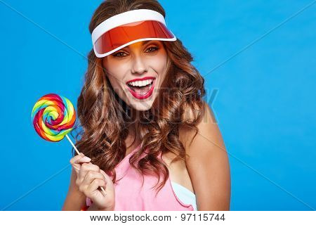 Beauty summer model girl Eating colourful lollipop on blue background