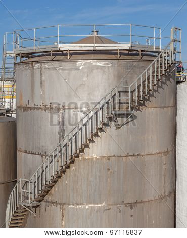 The Huge Petrol Oil Tanks With Stairs Exterior In Refinery Industry.