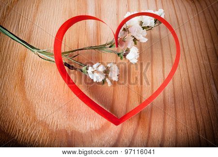 Red paper heart with white flower on wood background with natural pattern
