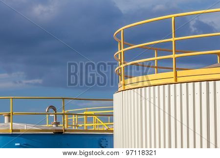 The Yellow Top Of Big Industrial Tanks Farm In Refinery Industry.